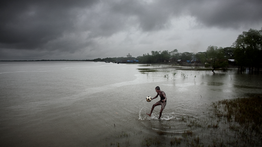 A BOY PLAYS FOOTBALL IN BANGLADESH, PADMA PAKUR, KHULNA DIVISION, 2009