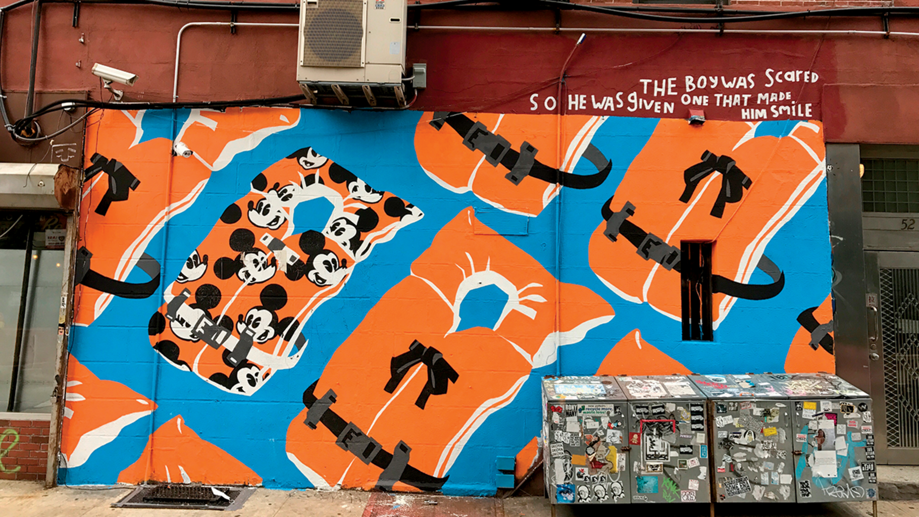 Sink or Swim by artist Adam Lucas was originally done in paint on bleached denim. He was later asked to reproduce the painting as a mural in New York City, as shown here. The work was inspired by an incident in May 2017 off the coast of Libya, when a boat overloaded with some 200 migrants capsized while attempting to reach Europe. Though many were rescued, several dozen died -- reportedly, most of them were very young children. The piece is in response to one specific disaster, but it can be applied to any number of refugee crises. The artist asks us to imagine being part of a family living in an environment so dire that the best hope lies across the uncertain sea. The Mickey Mouse life vest, representing joy and innocence, references an actual child making the journey as well as blameless youth being forced into a situation of such severity. Loss of childhood at best, loss of life at worst.