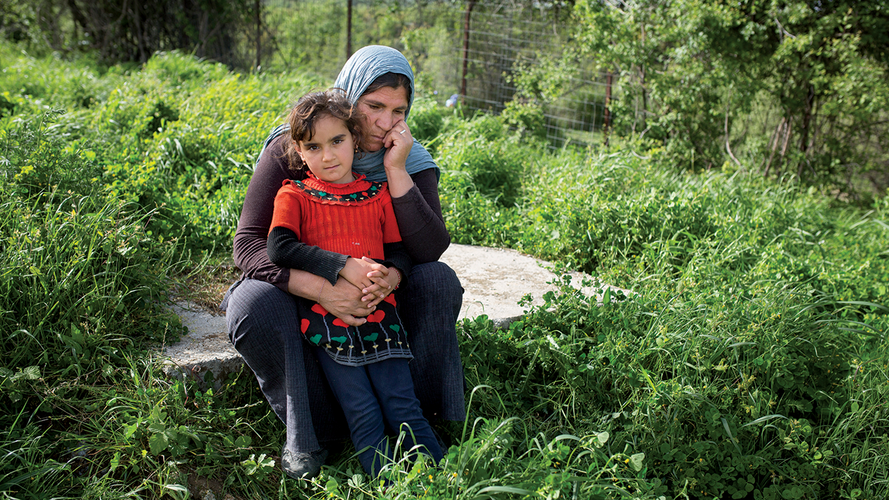Nurfa, a Yazidi refugee woman, with her granddaughter, Julia, at Petra Camp in Greece, after escaping ISIS attacks on their homes and villages in Iraq. Many Yazidis were killed during the attacks, while others were captured and enslaved. The lucky ones made it to Europe, where they found themselves, along with tens of thousands of other asylum-seekers, stuck in Greece.